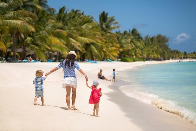Mooie moeder, zoon en dochter wandelen op het strand van de indische oceaan.