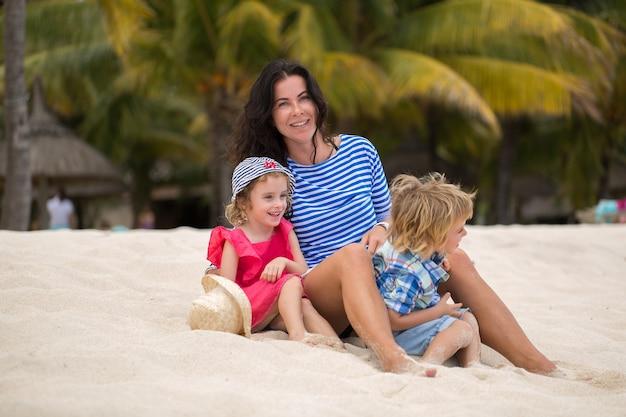 Mooie moeder, zoon en dochter zittend op de oceaan.