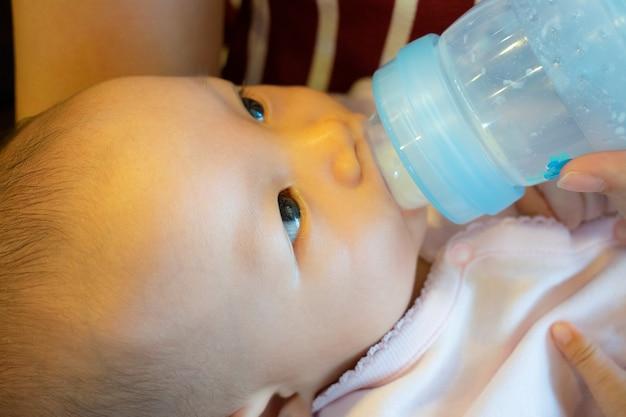 Mooie moederholding en voedende baby van fles, de jongen van azië.