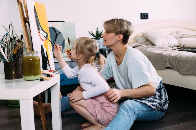 Mooie moederkunstenaar en haar kind schilderen thuis foto met acrylverf paint