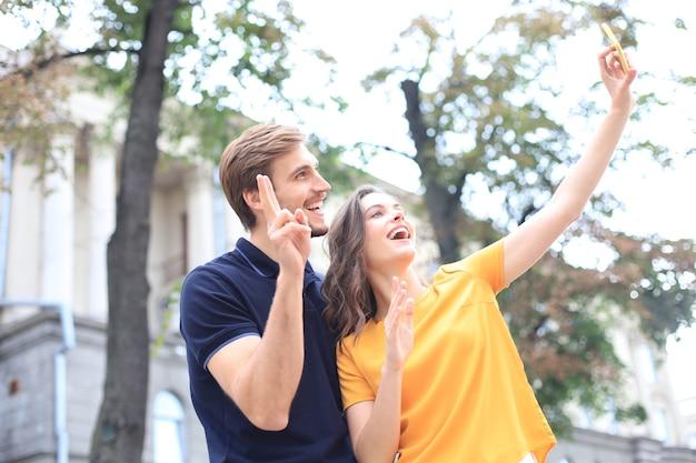 Mooie mooie jonge paar wandelen in de straten van de stad, knuffelen terwijl het nemen van een selfie.