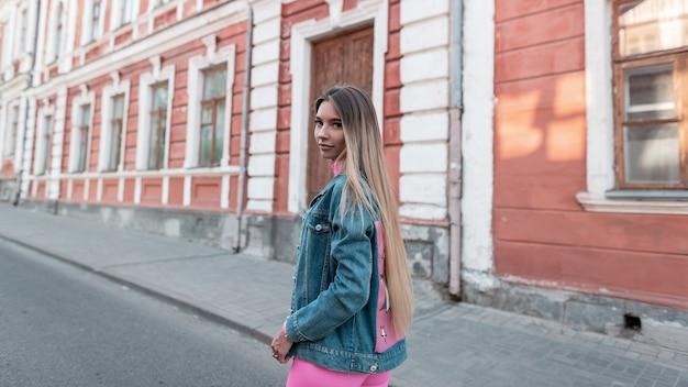 Mooie mooie jonge vrouw een modieuze blauwe denim jasje in een roze glamour korte broek lopen op straat op een warme zomerdag. leuk modern meisje buitenshuis. retro stijl trendy dameskleding.