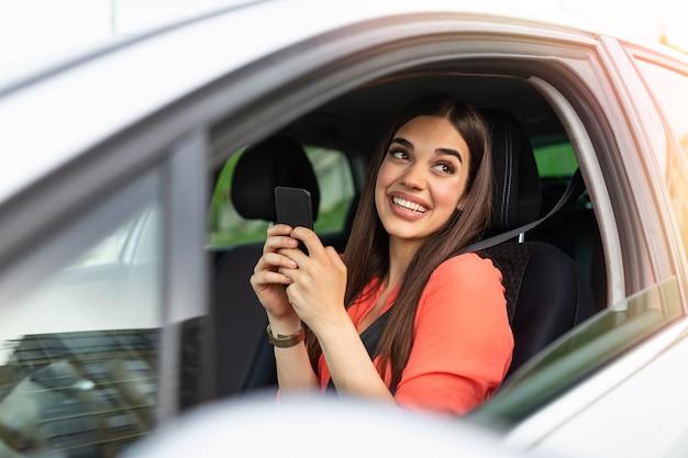Mooie mooie jonge vrouw glimlach en gebruik mobiele telefoon het scherm in de auto aan te raken tijdens het reizen.