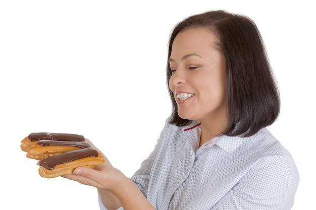 Mooie mooie jonge vrouw met chocolade eclair op een witte achtergrond