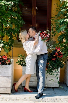Mooie mooie volwassen kussend paar, man en vrouw in elegante kleding, staan oog in oog, omhelzen elkaar en genieten van hun wandeling in de prachtige oude stad