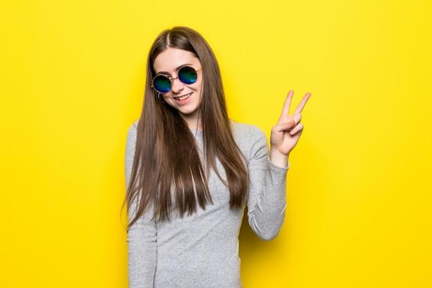 Mooie mooie vrouw die makend v-teken dichtbij ogen tonen die elegante die kleding dragen op gele muur wordt geïsoleerd