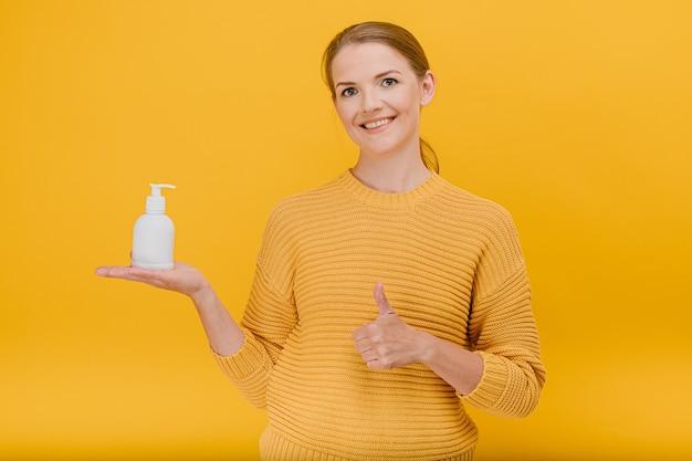 Mooie mooie vrouw die nonchalant gekleed is, gebruikt een antiseptisch ontsmettingsmiddel of vloeibare zeep