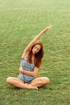 Mooie mooie vrouw doet yoga oefeningen in het park. gezond en yoga concept. fitness en sport