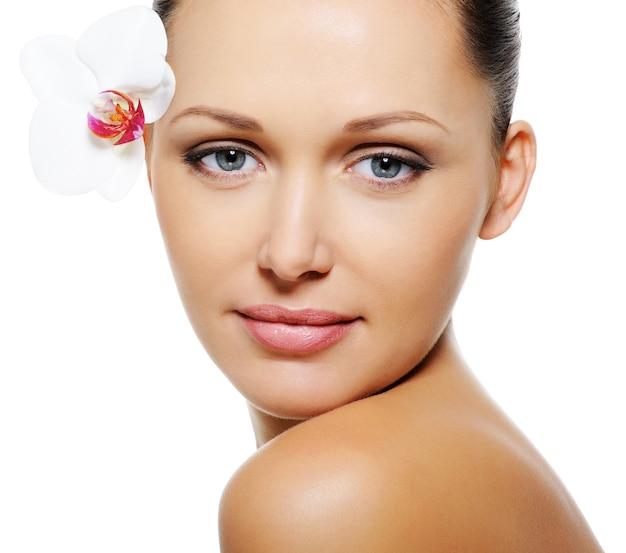 Mooie mooie vrouw met duidelijke huid en bloem dichtbij haar ogen