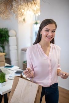 Mooie mooie vrouw met tassen tijdens het terugkomen van winkelen