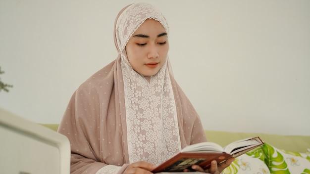 Mooie moslim die de koran leest zittend op de bank