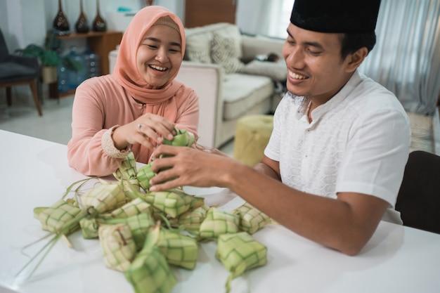 Mooie moslim paar aziatische ketupat rijstwafel thuis maken met behulp van palmblad