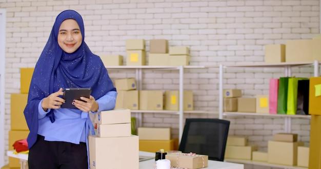 Mooie moslim vrouwelijke merchandiser doet online marketing op kantoor.