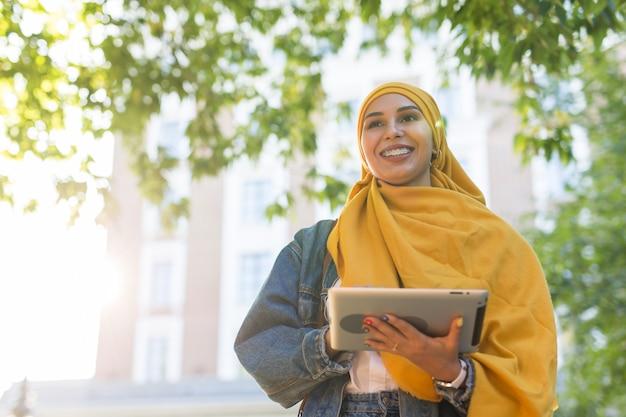 Mooie moslim vrouwelijke student helder gele hijab houden tablet dragen