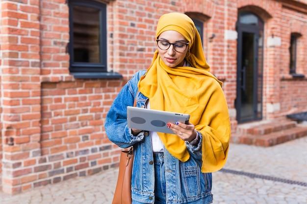 Mooie moslim vrouwelijke student met tablet