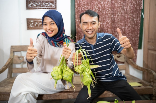 Mooie moslimfamilie en vriend die thuis ketupat-rijstwafel maakt met palmblad voor eid fitr mubarak-traditie die duim omhoog laat zien