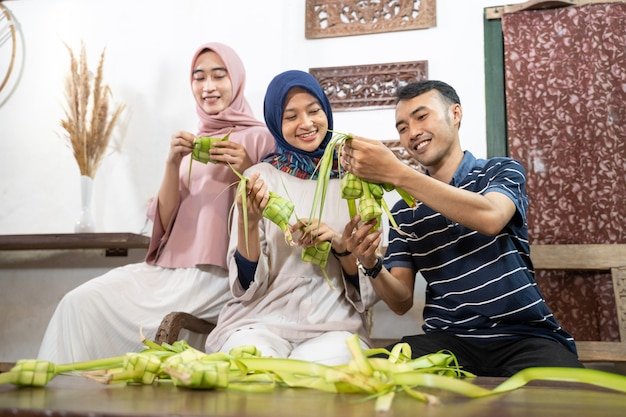 Mooie moslimfamilie en vriend die thuis ketupat-rijstwafel maakt met palmblad voor eid fitr mubarak-traditie Premium Foto