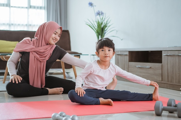 Mooie moslimmoeder en dochter trainen samen om gezond te worden. familievrouw en kind genieten van thuis oefenen