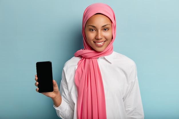 Mooie moslimvrouw adverteert moderne gadget, houdt slimme telefoonapparaat met leeg scherm voor uw advertentie, draagt traditionele sluier op hoofd