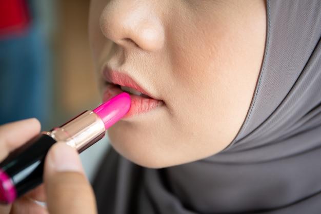 Mooie moslimvrouw die lipstock op haar mond toepast