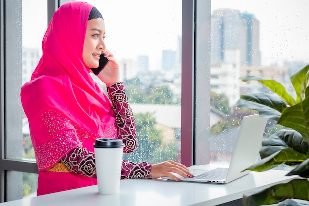 Mooie moslimvrouw die met telefoon op koffiewinkel spreekt.