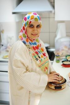 Mooie moslimvrouw die zich in keuken bevindt