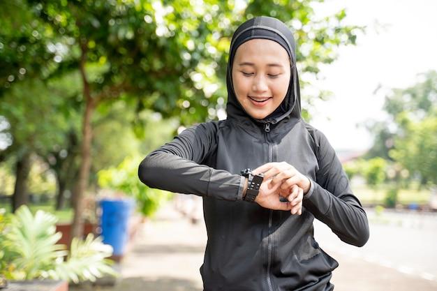 Mooie moslimvrouw haar hartslag op slimme horloge tijdens het sporten buiten