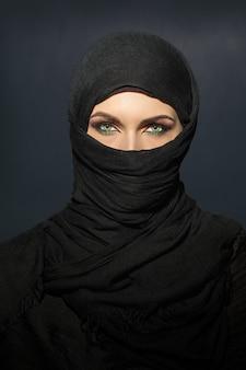 Mooie moslimvrouw in niqab traditionele sluier tegen op donkere achtergrond