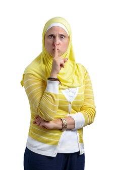 Mooie moslimvrouw met geïsoleerde stiltegebaar