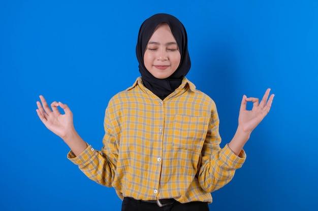 Mooie moslimvrouw met haar handen gebaren en haar ogen sluiten