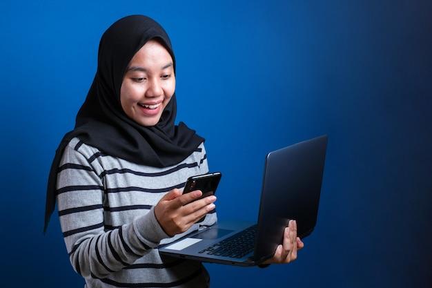 Mooie moslimvrouw sms't met smartphone over geïsoleerde achtergrond met een gelukkige uitdrukking terwijl ze laptop over blauwe achtergrond houdt