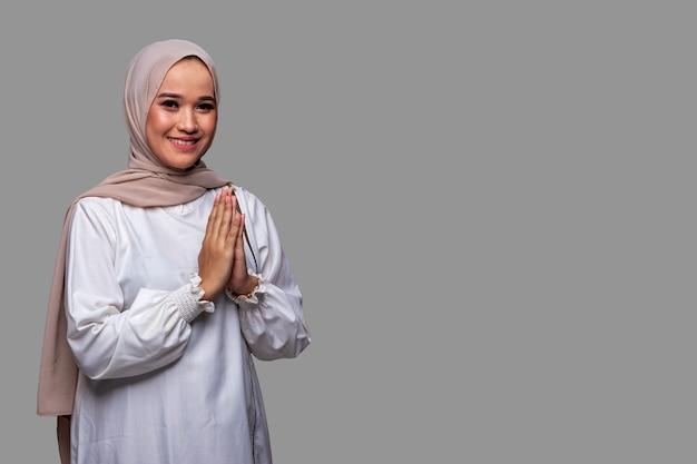 Mooie moslimvrouwen die hijab dragen en eid alfitr vieren geïsoleerd