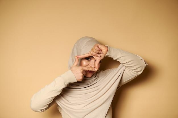Mooie moslimvrouwen in hijab maken een lijst met vingers en kijken erdoorheen