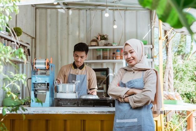 Mooie moslimvrouwenondernemer bij haar kleine voedselkraam die naar camera glimlacht