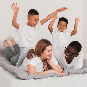 Mooie multiculturele familie die in bed blijft