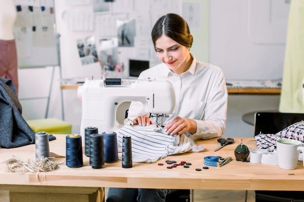 Mooie naaister naaien op haar atelier. naaister bezig met de naaimachine. kleermaker die een kledingstuk maakt in haar werkplaats.