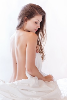 Mooie naakte vrouw die in bed ligt en voor zich het behandelen met wit blad