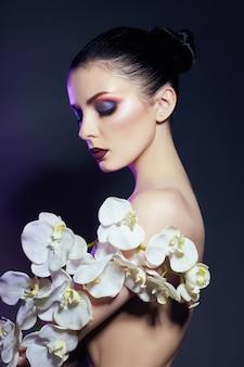 Mooie naakte vrouw met een tak van witte orchidee