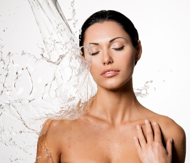 Mooie naakte vrouw met nat lichaam en spatten van water