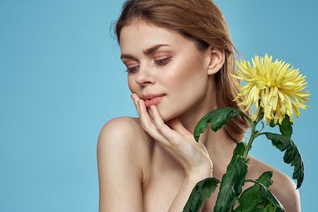 Mooie naakte vrouw schouders gele bloem bedel blauw