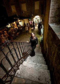 Mooie nachtopname van sexy vrouw in jurk die de trap op loopt op straat