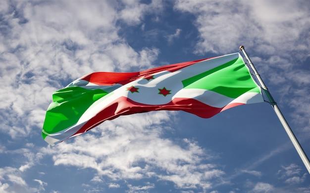 Mooie nationale vlag van burundi wapperen op hemelachtergrond.