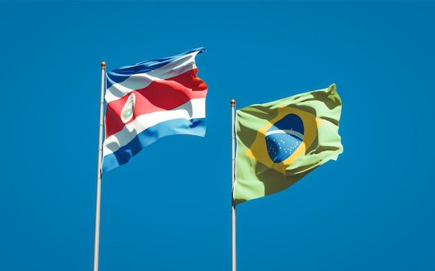 Mooie nationale vlaggen van brazilië en costa rica samen op blauwe hemel