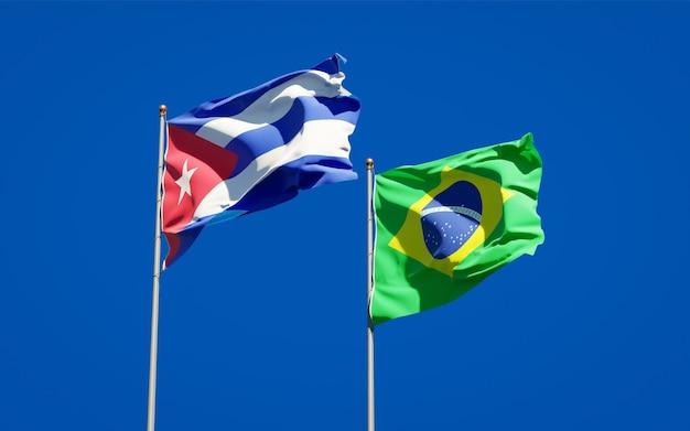 Mooie nationale vlaggen van brazilië en cuba samen op blauwe hemel