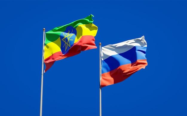 Mooie nationale vlaggen van ethiopië en rusland samen op blauwe hemel. 3d-illustraties