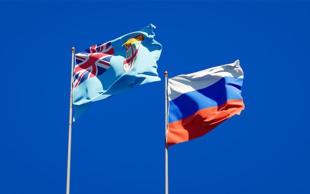 Mooie nationale vlaggen van fiji en rusland samen op blauwe hemel. 3d-illustraties