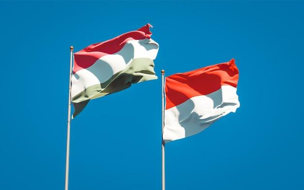 Mooie nationale vlaggen van hongarije en indonesië samen op blauwe hemel