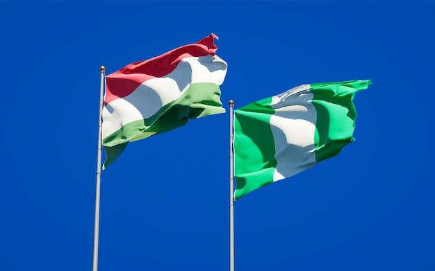 Mooie nationale vlaggen van hongarije en nigeria samen op blauwe hemel
