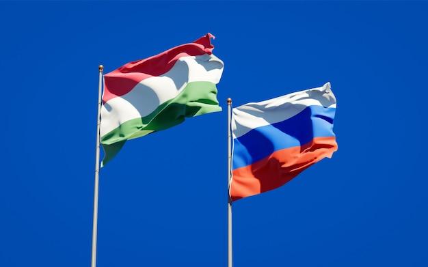 Mooie nationale vlaggen van hongarije en rusland samen op blauwe hemel. 3d-illustraties