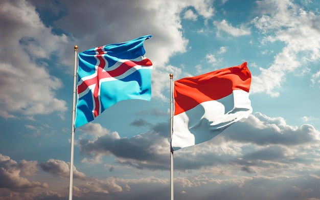 Mooie nationale vlaggen van ijsland en indonesië samen op blauwe hemel
